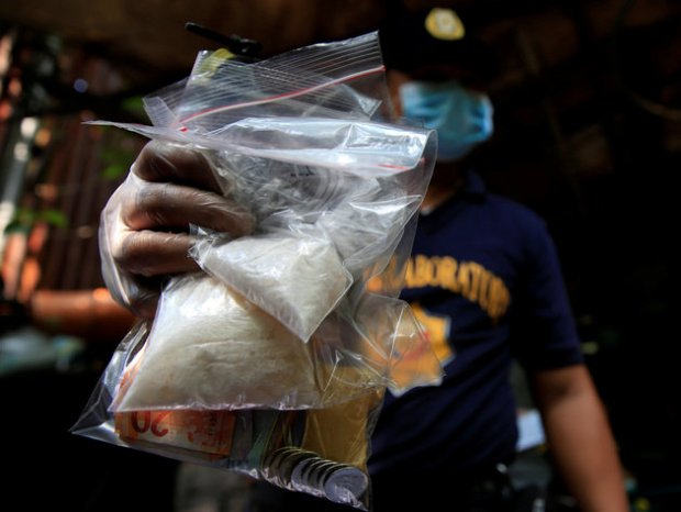 A member of the Philippine National Police (PNP) investigation unit shows confiscated methamphetamine, known locally as Shabu, along with Philippines pesos seized from suspected drug pushers during an operation by the police in Quiapo city, metro Manila