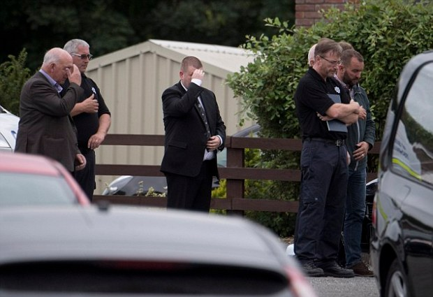 A prayer is said as the bodies of the victims are brought out of the house in Ballyjamesduff.jpg