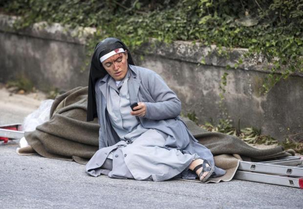 Italian earthquake1: A nun checks her phone as she lies near a victim laid on a ladder