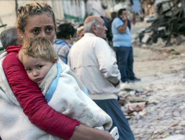 Italian Earthquake12: A woman holds a child as they stand in the street following an earthquake, in Amatrice, Italy, Wednesday