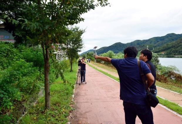 A photographer points at where the body of Lotte Group Vice Chairman Lee In-won was found in Yangpyeong