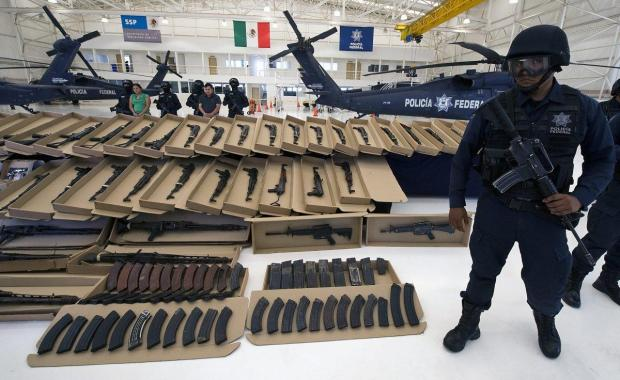 A Mexican Federal Police stands guard with a cache of weapons seized from Los Zetas1.jpg