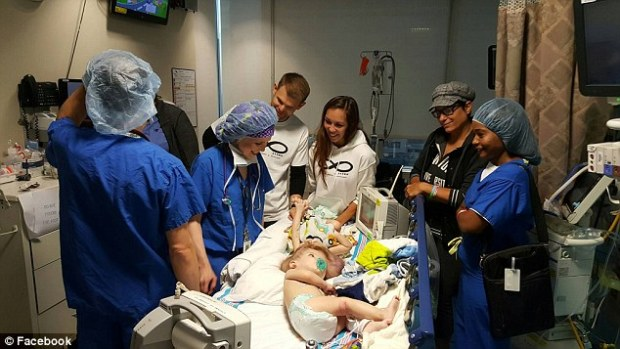Parents Nicole and Christian (in white) as the twins are prepped for their surgery,Thursday1.jpg