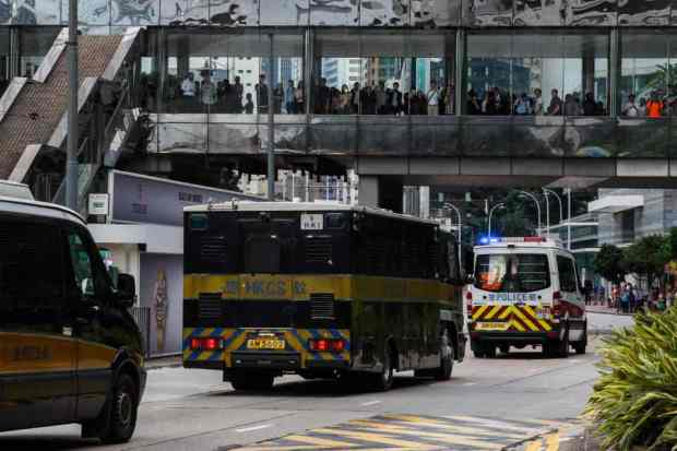 a-van-carrying-jutting-leaves-the-high-court-escorted-by-a-police-convoy-in-hong-kong