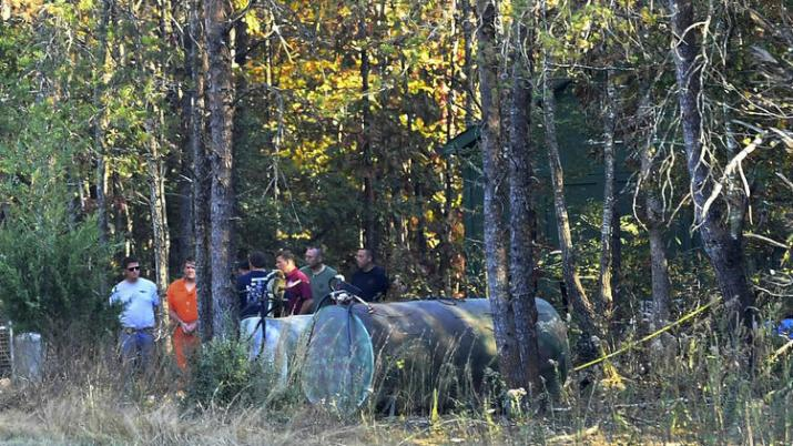 todd-kohlhepp-in-handcuffs-and-an-orange-jumpsuit-is-escorted-by-deputies-on-his-property-in-woodruff-s-c-on-saturday-nov-5-2016