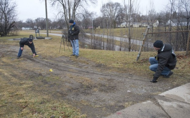 Damarlon Thomas officers measure tire tracks and search for spent shell casings1.jpg