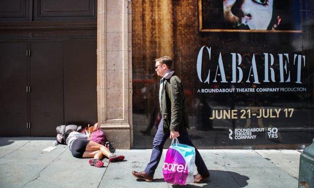 a-man-walks-by-a-homeless-woman-sleeping-on-the-sidewalk-san-franciscos-tenderloin-district