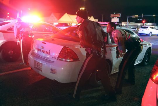 Cops and protesters alike, duck behind police cars as shots are fired outside of Ferguson Market in Ferguson on Sunday1.jpg