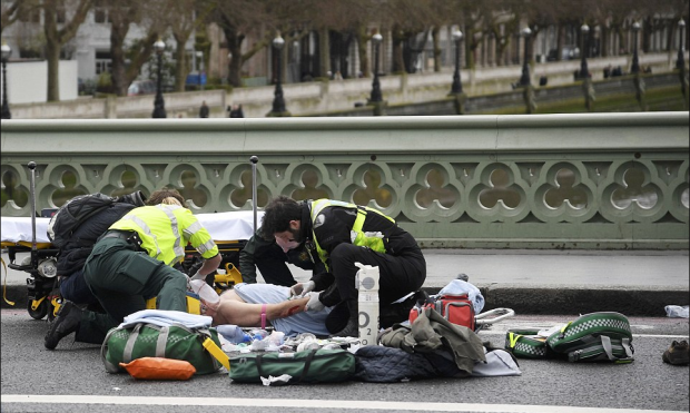 EMTs attend to unidentified victim knocked down on Westminster Bridge where around a dozen pedestrians were knocked down by the car.png