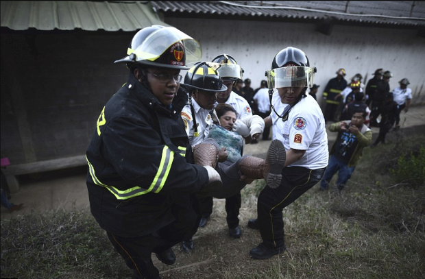 Firefighters carry a woman who fainted outside a reformatory for youth and men, Centro Correccional Etapa II, where a riot and fire in Guatemala City, Sunday.png