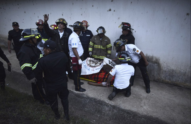 Firefighters surround the body of a victim inside a reformatory at the correctional facility 12 miles outside of Guatemala City.png