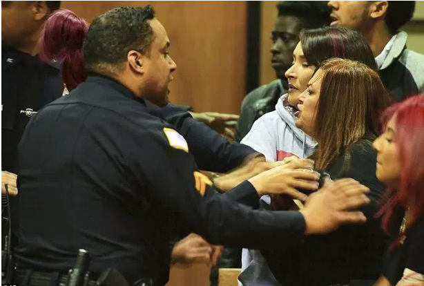 Police officers then stepped in to separate the two parties inside the court room .png