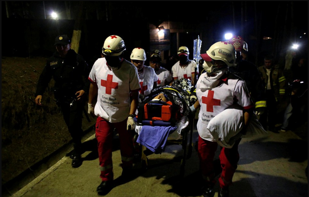 Red Cross EMTs carry a guard injured after a riot by underage inmates at the Guatemalan prison on Sunday .png
