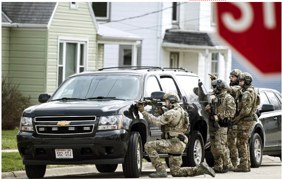 FBI agents are seen above on Thursday providing tactical support to sheriff's detectives during a search for Jakubowski in Janesville, Wisconsin.png