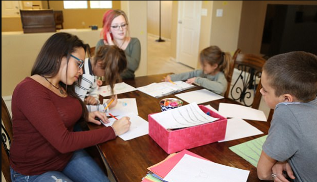 Cristina and Sierra tackle homework with the kids.png