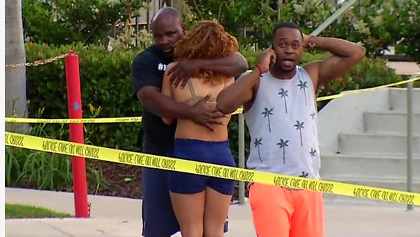 Grief stricken poolside party goers comfort each other after seven people were shot by gunman