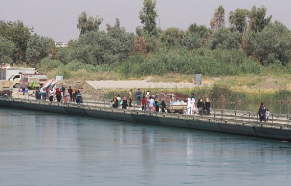 Iraqi civilians flee combat zone through a floating bridge West of Mosul 1