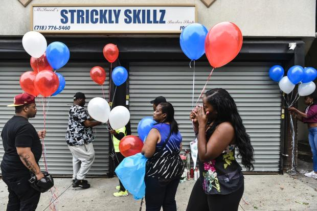 Mourners contribute candles and flowers ant Strickly Skillz barber shop in Queens for Zanu Simpson who was fatally shotsitting in his vehiclee 2. .jpg