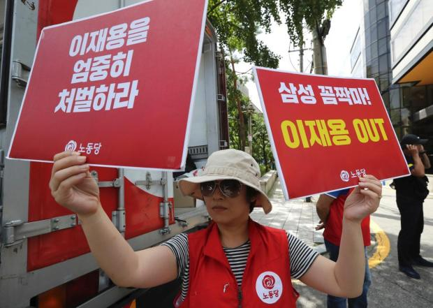"""A protester holds banners reading """"Out, Lee Jae-yong""""  1.jpg"""