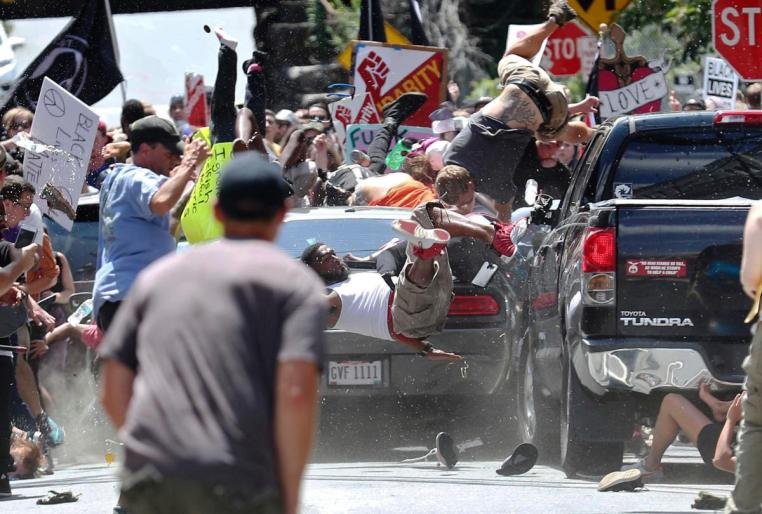 People fly into the air as a vehicle drives into a group of protesters demonstrating against a white nationalist rally in Charlottesville, Va., Saturday, Aug. 12,