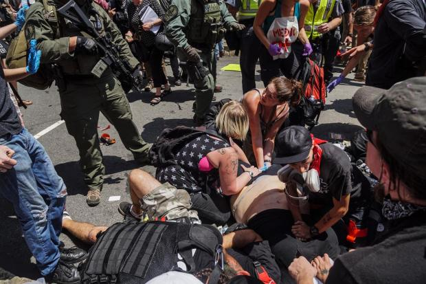 People tend to a counter-protester lying on the ground after he was hit by a car.jpg