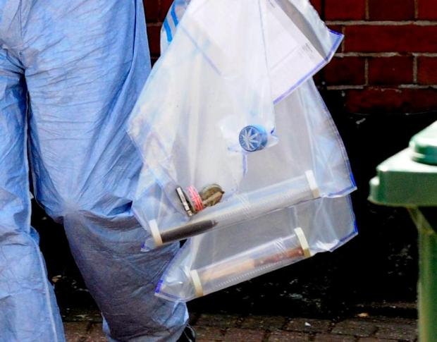 Police Forensics team removing items from the house in North London in evidence bags 2